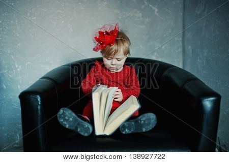 Little Cute Princess Girl Sitting On A Chair And Read Old Book