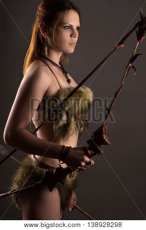 beautiful woman archer with bow isolated on gray