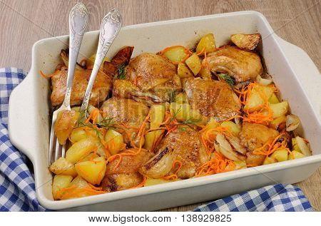 Braised roast chicken and vegetables in ceramic roasting pan