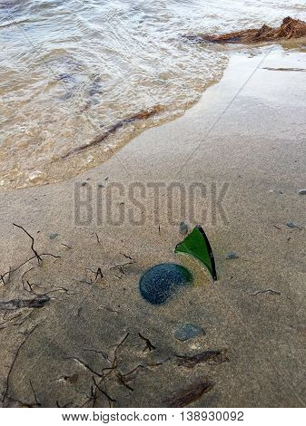 One broken bottle at the beach, very dangerous to go swimming