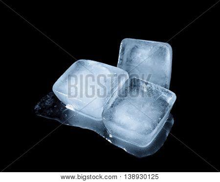 Melting ice cubes on dark background