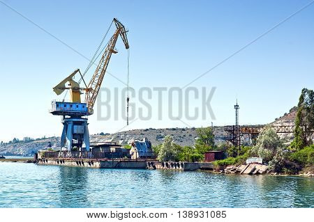The crane on the floating dock in the harbor. Plenty of cargo ships needs oil and equipment for the long journey by sea.