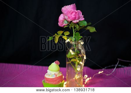 rose with cup cake, blake background and lights