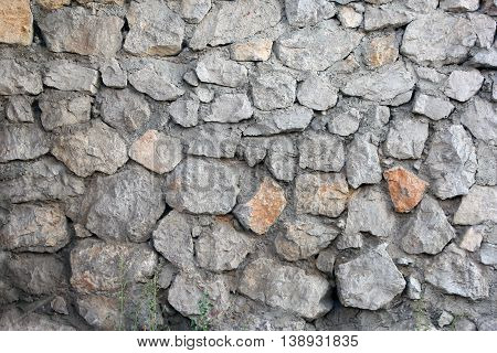stone masonry wall from old dilapidated shabby rubble foreground closeup in Crimea