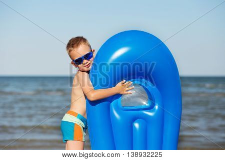 Little Kid Holding An Inflatable Mattress On The Beach On Hot Summer Day.