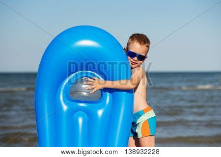 Smiling Boy Playing On The Beach With Air Mattress