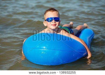 Little Kid Swimming In The Sea On Inflatable Mattress