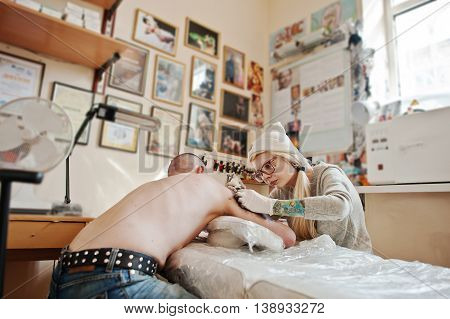 Young blonde woman master tattooist in glasses and hat with tattoo machine at hands make tattoo Dreamcatcher at hand of man.