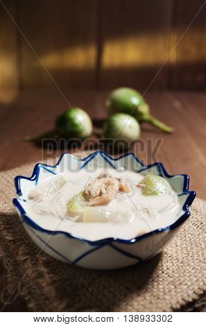 Soup made from coconut milk with shrimp and vegetable on wooden table background in still life tone and low key tone