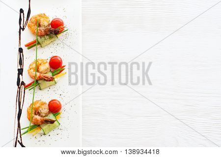 Top view on plate with fried prawns with vegetables on white wooden background, free space for advertisement. Vertical orientation of shrimp meal