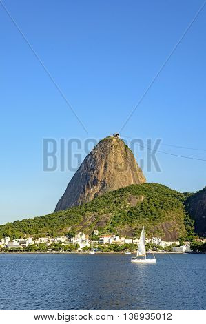 Small sailboat sailing the bay of Guanabara and passing in front of the hill of Sugar Loaf