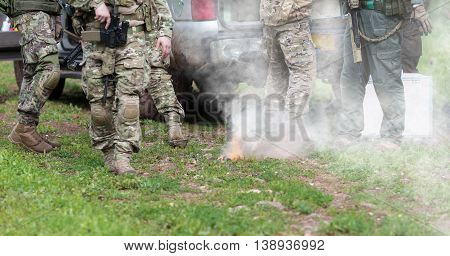 men in military uniform with weapon are campfire