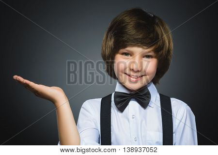 Happy child keeps on hand thing. Closeup Portrait of handsome boy smiling isolated on grey background