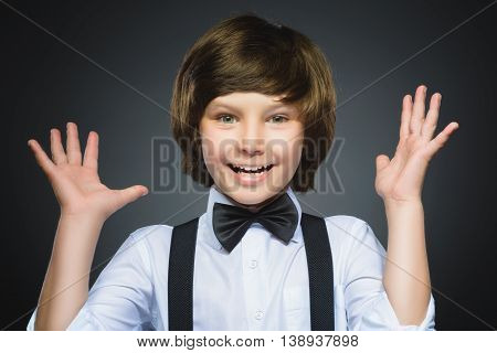 Closeup Portrait of happy boy going surprise isolated on gray background.