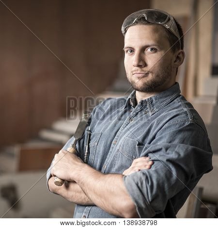 Portrait of young carpenter proud of his project