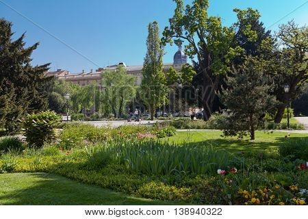Zagreb park with trees and flowers and three people on segway