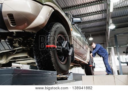 Tire clamped with aligner undergoing auto wheel alignment in garage. Electronic tuning of car