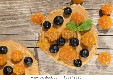 toast of white bread with peanut butter and berries cloudberries and blueberries