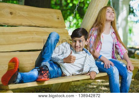 Smiling girl and boy having fun at playground. Children playing outdoors in summer. Teenagers on a swing