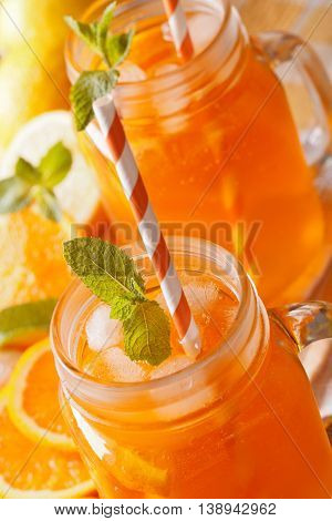 Refreshing Cocktail With Oranges, Lemons, Ice In A Glass Jar Macro. Vertical