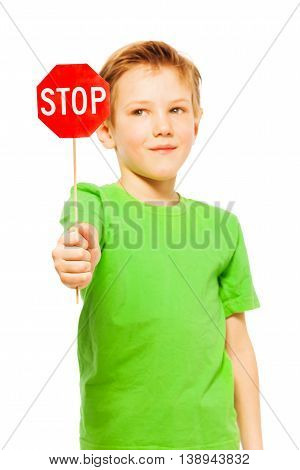 Close-up portrait of young fair-haired boy in green tee, holding small red Stop sign, isolated on white