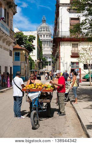 HAVANA,CUBA - JULY 17,2016 :  Street scene with a man selling tropical fruit near the Capitol in Old Havana
