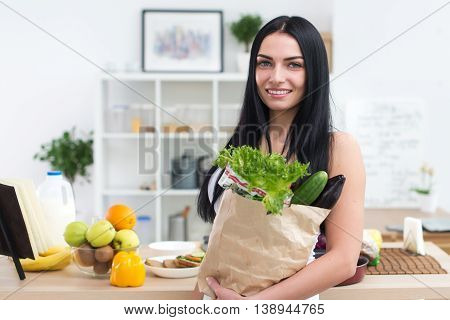 Close-up portrait of a woman holding paper bag full of fresh vegetables. Happy smiling female vegetarian with fresh grocery