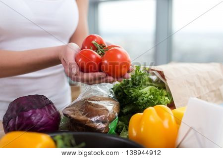 Female hands of a caucasian cook holding red tomato bunch over kitchen worktop with fresh grocery and rye bread on it