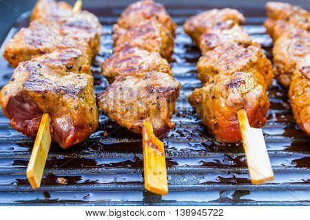 pan fried round steak cubes on sticks in a grill pan