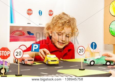 Smiling five years old boy playing driver with toy paper cars in safety road class