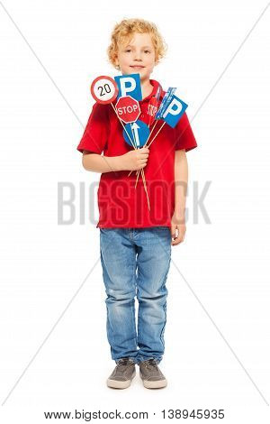 Full-length portrait of fair-haired schoolboy in red tee and denim, holding bunch of toy road signs, isolated on white