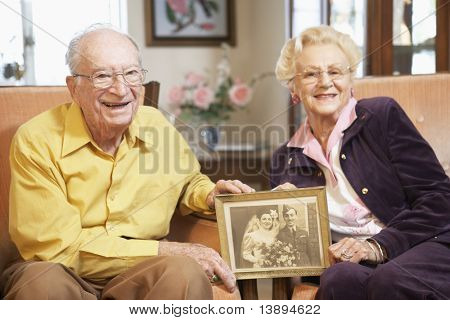 Senior couple holding wedding photo