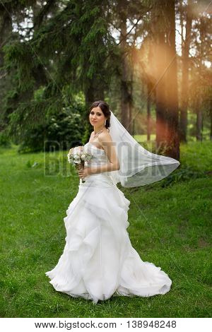 Beauty bride in bridal gown with bouquet and lace veil on the nature. Beautiful model girl in a white wedding dress. Female portrait in the park. Woman with hairstyle. Cute lady outdoors