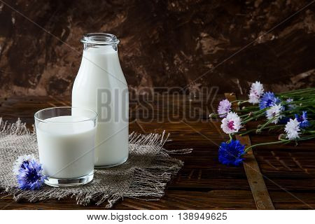 Bottle with milk and glass of milk at wooden table with lovely flowers. Style rustic.