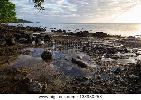 Sunrise over ocean tropical island. Clouds are reflected in water. Beqa Island. Fiji