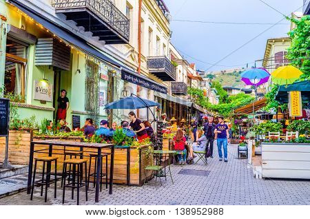 TBILISI GEORGIA - MAY 28 2016: The tourists enjoy the local cuisine on the summer terrace of cafe on May 28 in Tbilisi.