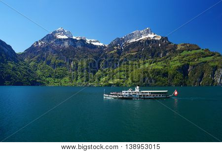 LAKE LUCERNE, SWITZERLAND - MAY 6, 2016: Liner filled with passengers. Calm mountain lake towered by snow covered peaks and fresh, green forest in the Swiss Central Alps.