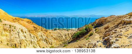 The rocky yellow slopes of Ein Gedi Nature Reserve with the bright blue waters of Dead Sea and mountains of Jordan on background Judean desert Israel.