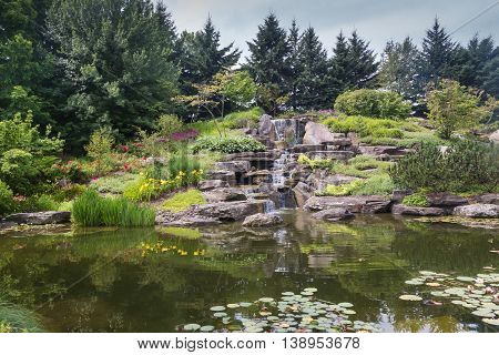 Calm water of a lake with a waterfall in a japanese garden surrounded by trees and plants. Meijer Garden Grand Rapids Michigan United States.