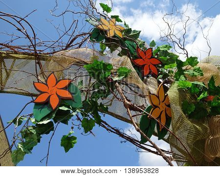 arch of rust, orange, yellow ochre, and carmel brown painted flowers nestled in burlap fabric and willow vines against a blue sky with white clouds in this floral display in Wisconsin