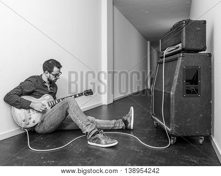 Photo of a man sitting playing his electric guitar in front of a large amplifier in a hallway. Black and white version.
