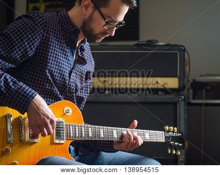 Photo of a man in his late 20's sitting in a studio playing his electric guitar.