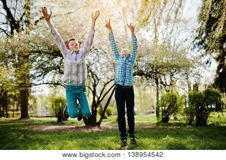 Two Brother Boy With Headphones Having Fun And Jump In Air On Park. Brother Love.