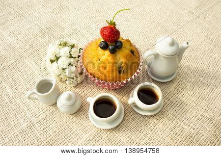 two cups of coffee and a muffin with berries