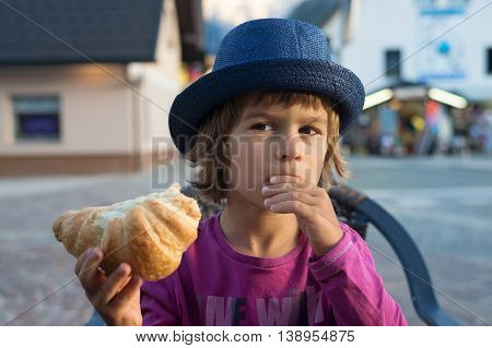 Cute little boy with blue hat sitting at the table eating tasty croissant.