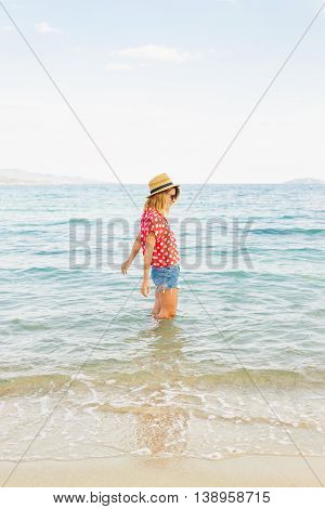 Beautiful woman playing with waves from ocean during vacation holiday