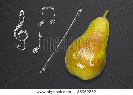 Creative concept photo of a pear as a violin with illustrated bow and notes on black background.