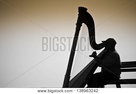 Vancouver Canada - June 26, 2009 : Musician harpist performer silhouette sit on a bench near the sea in Vancouver Canada