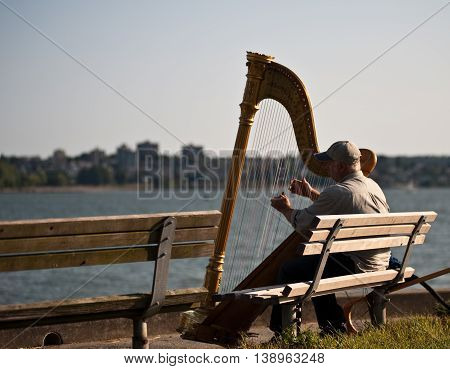 Vancouver Canada - June 26, 2009 : Musician harpist performer sit on a bench near the sea in Vancouver Canada