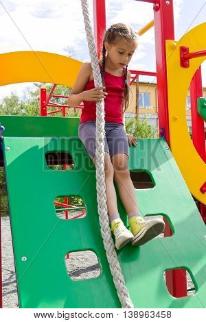 Little caucasian girl dressed in red jersey playing on playground, sliding down the wooden wall with a rope